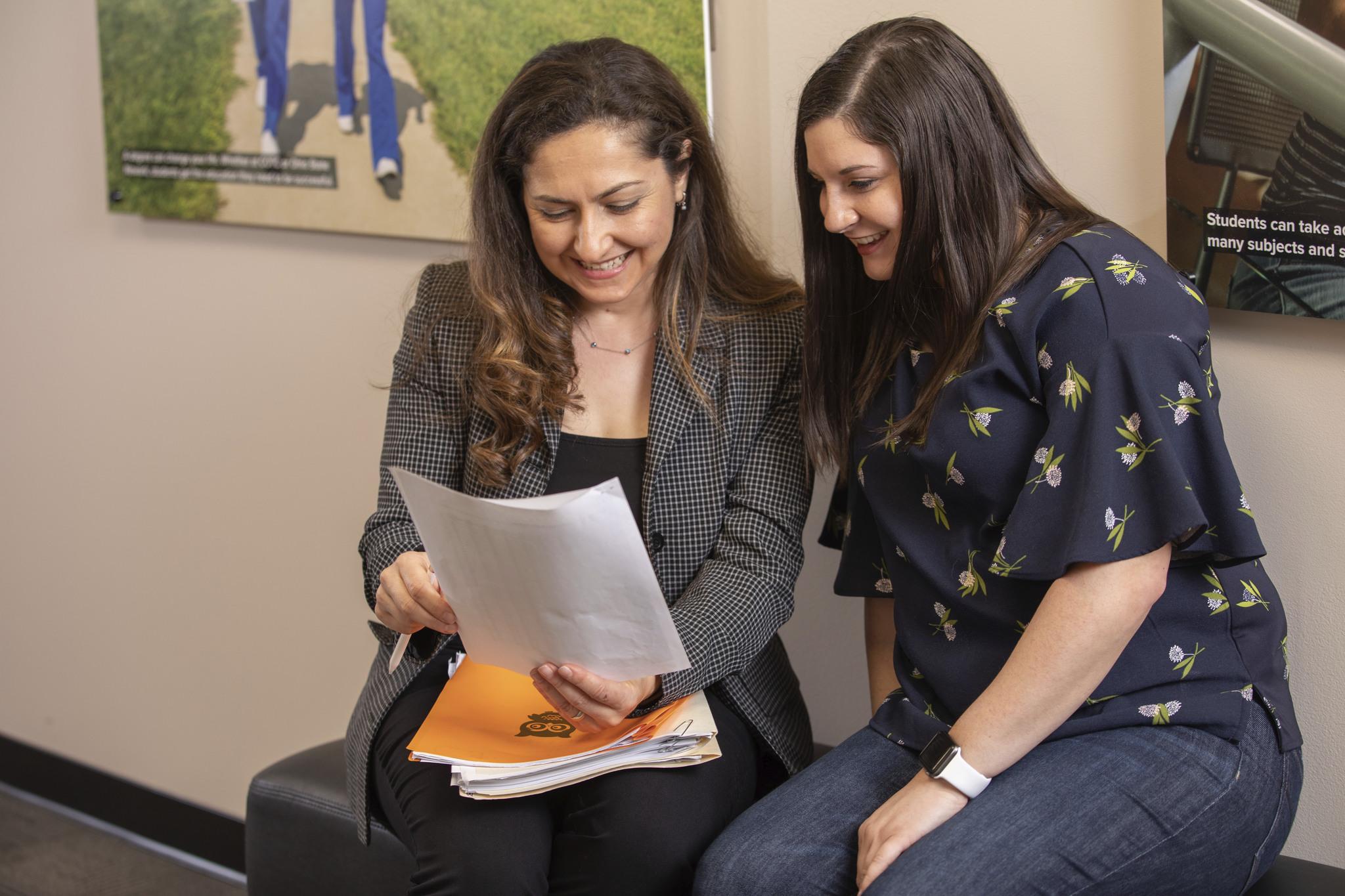Associate Professor Asuman Turkmen sits with a student.